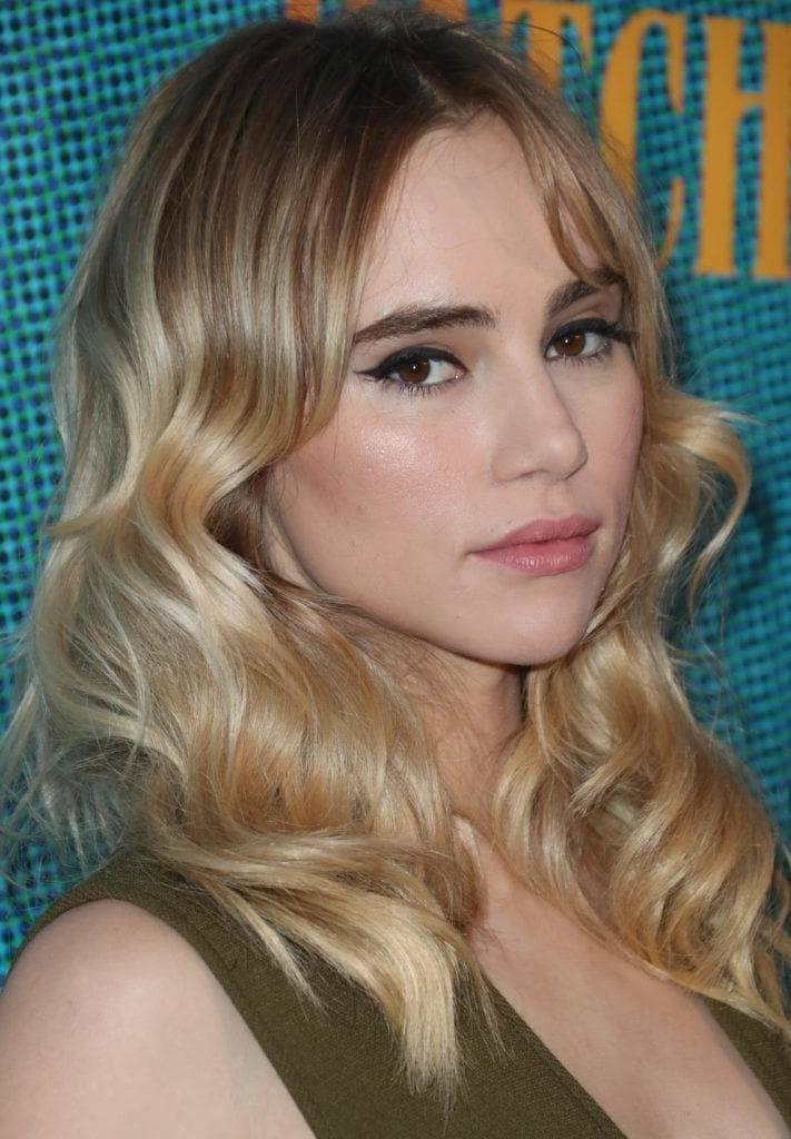 Nuances de cheveux blonds : Suki Waterhouse avec des cheveux blonds ondulés à balayage de longueur moyenne avec une longue frange centrale.