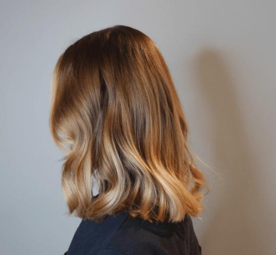 vue de côté d'une femme aux cheveux longs aux épaules avec des vagues et différentes nuances de blond