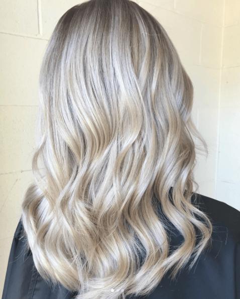 Vue arrière des longs cheveux blonds d'une femme aux tons de blond perlé