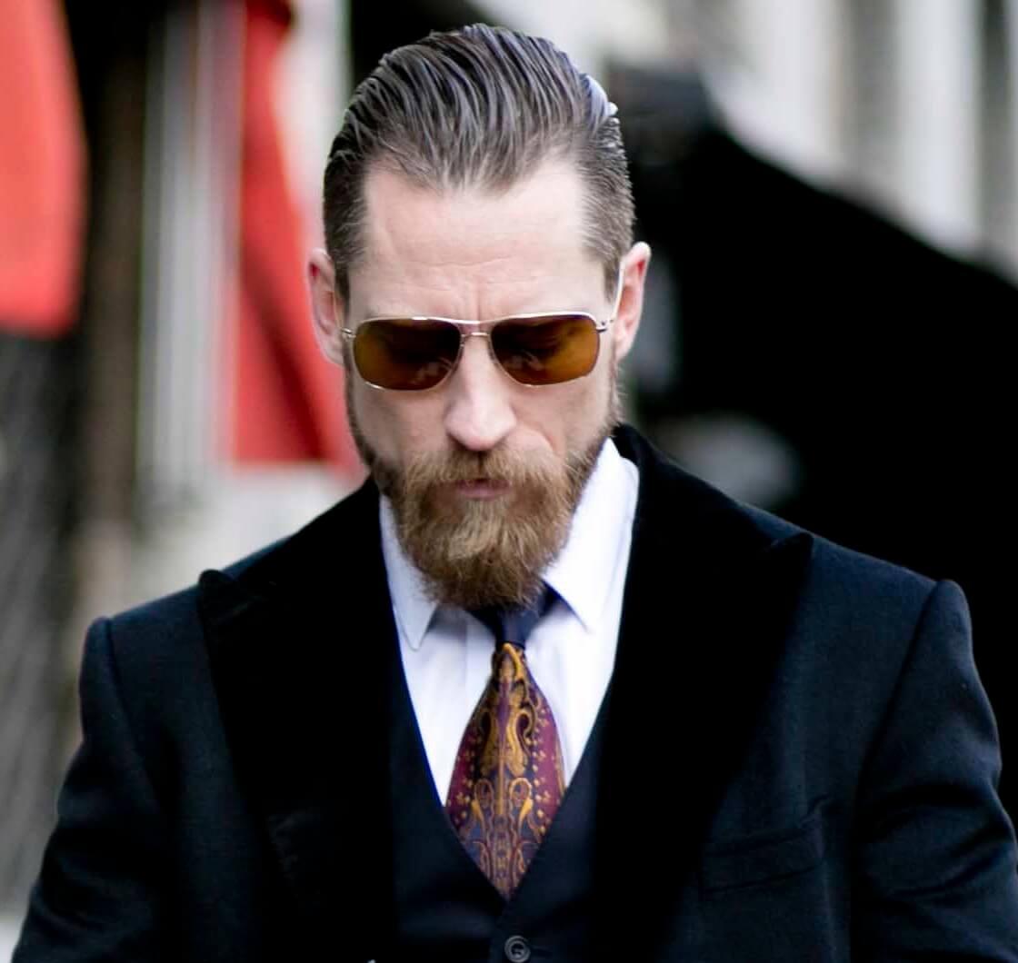 vue de face d'un homme barbu et aux cheveux bruns lissés vers l'arrière