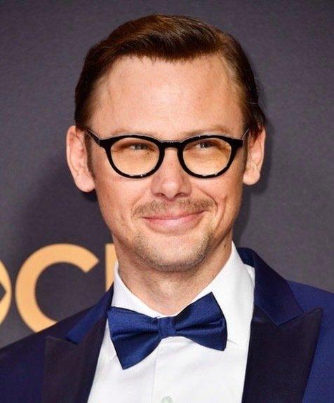 Coiffures pour hommes aux cheveux fins : Jimmi Simpson portant des lunettes et une cravate noire et les cheveux en arrière.