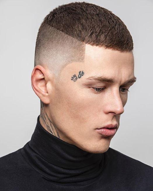 Coiffures pour hommes aux cheveux fins : Modèle avec des cheveux bruns, hauts et courts, serrés, portant un col roulé noir.