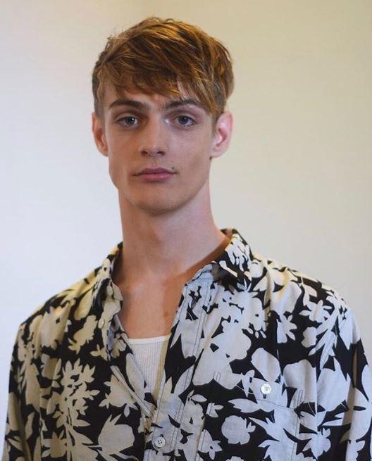 Coiffures pour hommes aux cheveux fins : Modèle avec des cheveux blonds, des côtés courts et un long haut en désordre, portant une chemise à fleurs audacieuse.