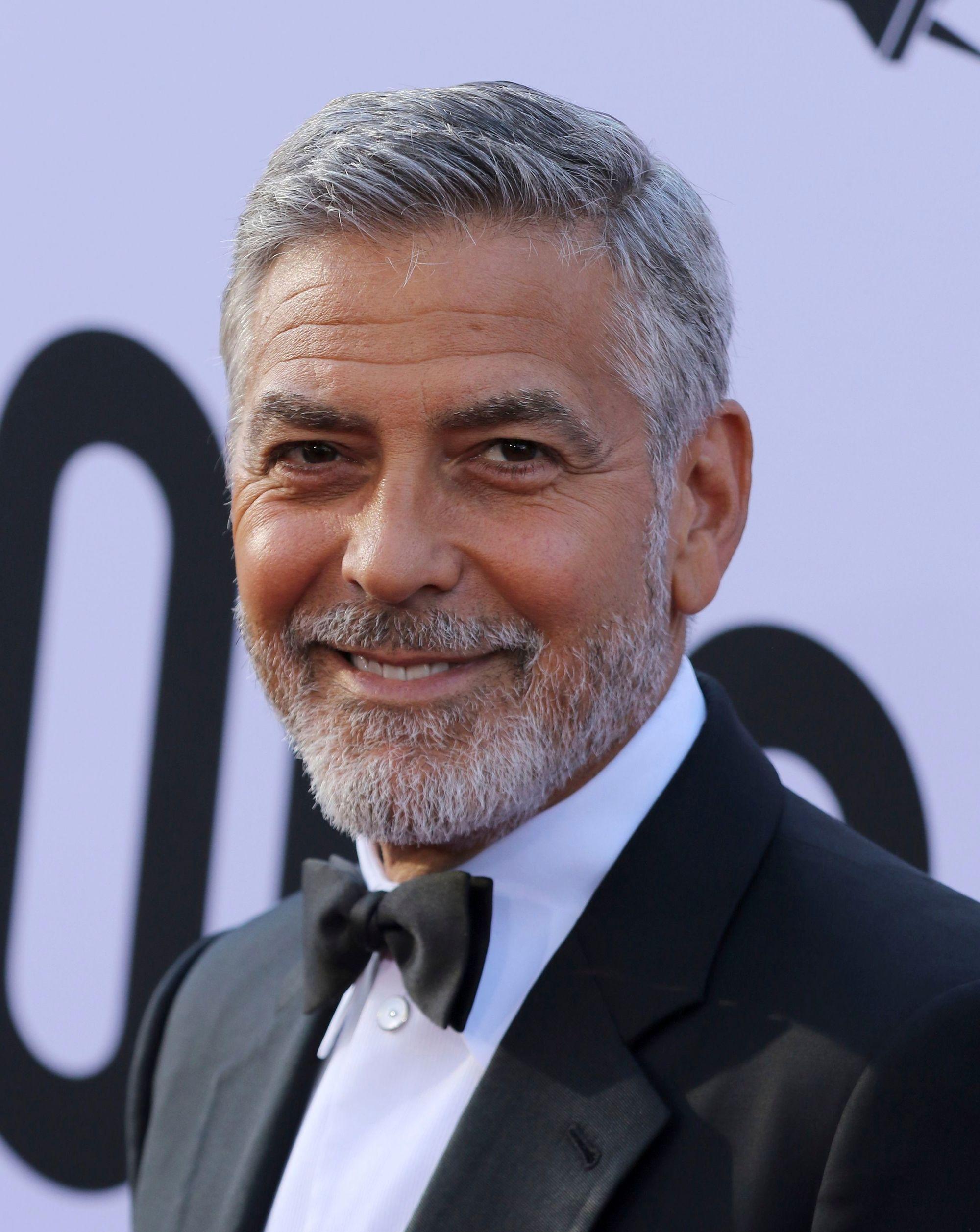 Coiffures pour hommes de plus de 50 ans : George Clooney avec un peigne court et effilé et une barbe grise, portant un costume élégant.