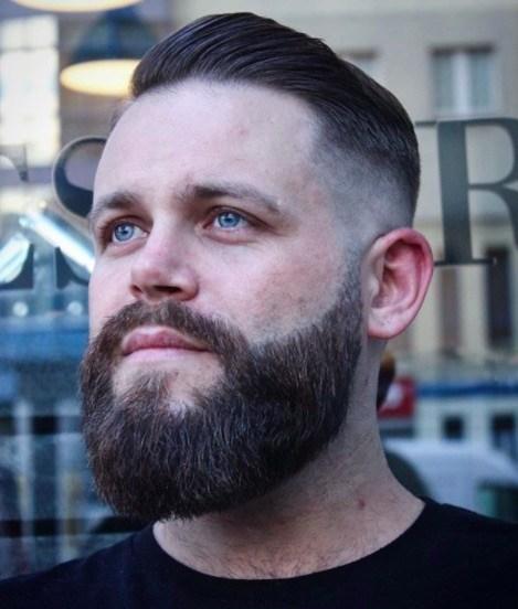 Coiffures pour hommes aux cheveux fins : Homme avec une moustache barbue et des cheveux bruns coupés en dessous