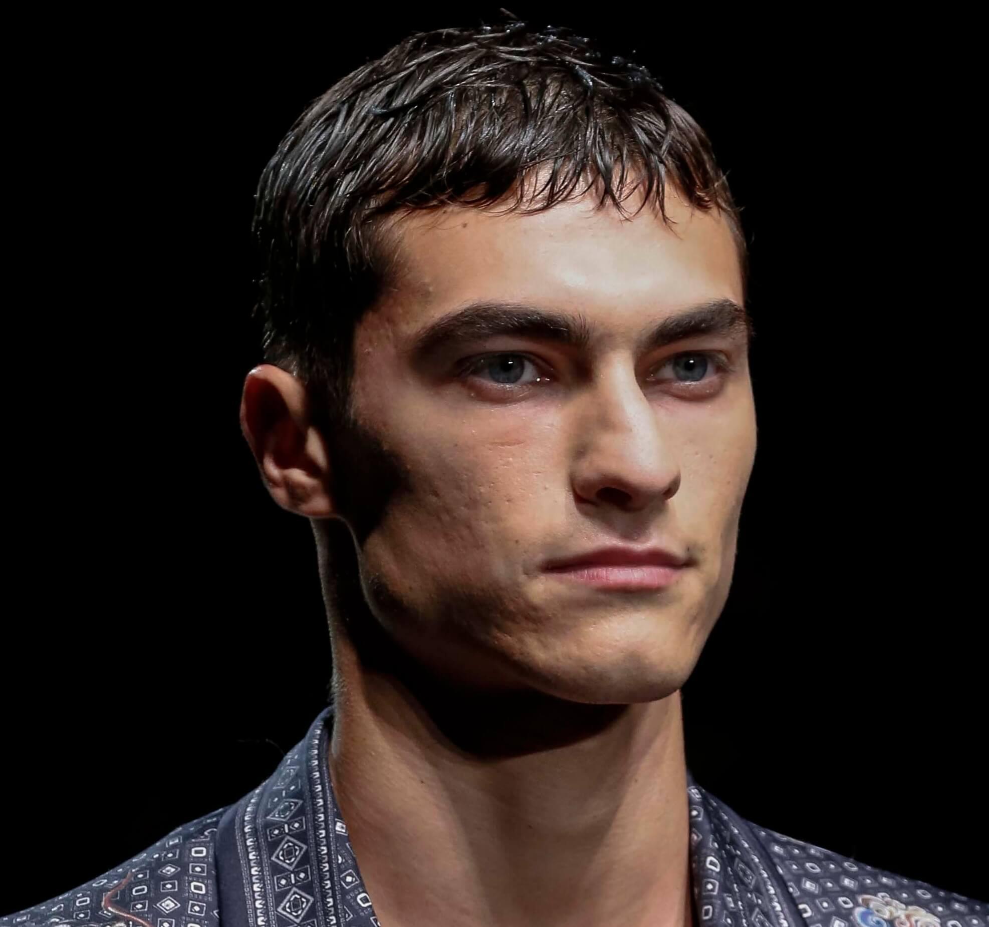 Modèle masculin aux cheveux foncés avec une coupe de César à l'aspect mouillé