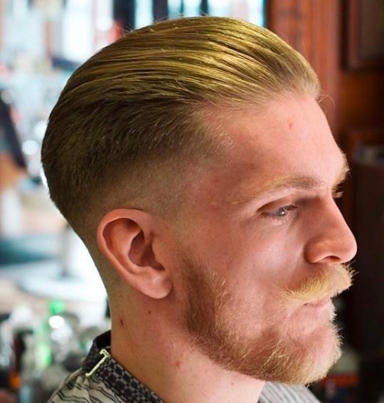Coiffures pour hommes aux cheveux fins : Homme aux cheveux roux brossés sur le dos, barbe et moustache taillées