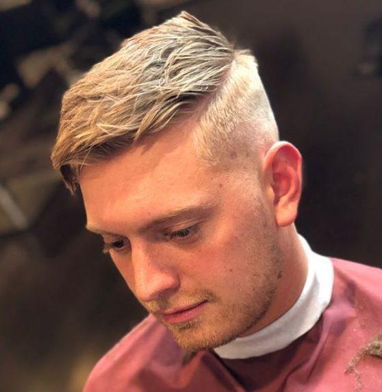 Homme blond avec raie sur le côté et coupe de cheveux dégarnie