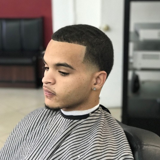 profil latéral d'un homme avec une coupe de cheveux courte et pointue