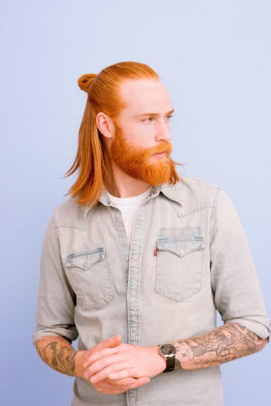 Un homme avec un chignon et une barbe : Un homme roux aux cheveux longs dans un chignon d'homme à barbe mi-haute mi-inférieure, portant une chemise en jean et posant sur un fond lilas