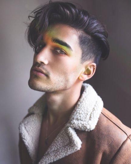 un homme brun en veste de mouton bronzée avec des cheveux souples et un décolleté