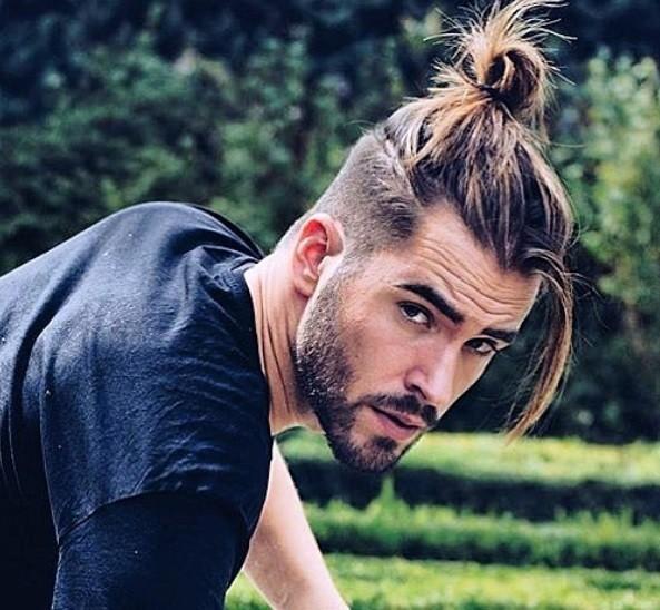 décoloration de la coupe d'un homme en chignon : gros plan d'un homme à la coupe effilée, avec quelques cheveux tombant en vrac devant son visage, portant une chemise noire et posant à l'extérieur