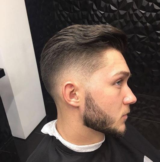 homme aux cheveux bruns chez les coiffeurs avec une cape noire enroulée autour de lui et ses cheveux en pompadour ondulé et soigné s'effacent