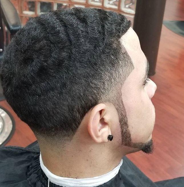 cheveux bruns courts et ondulés, avec une coupe effilée