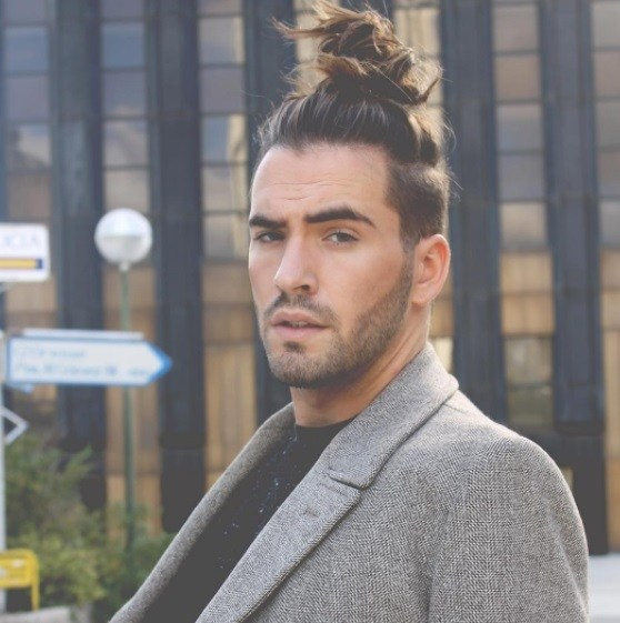 top knot men : modèle masculin avec une coiffure de top knot désordonnée portant un costume
