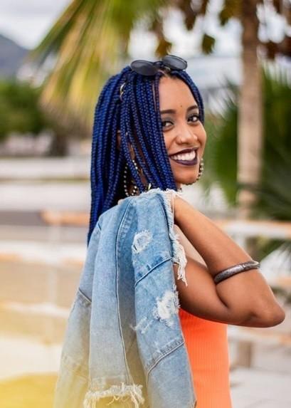 Longues tresses de boîte : Une jeune fille souriante avec de longues tresses bleues, tenant une veste en denim sur son épaule