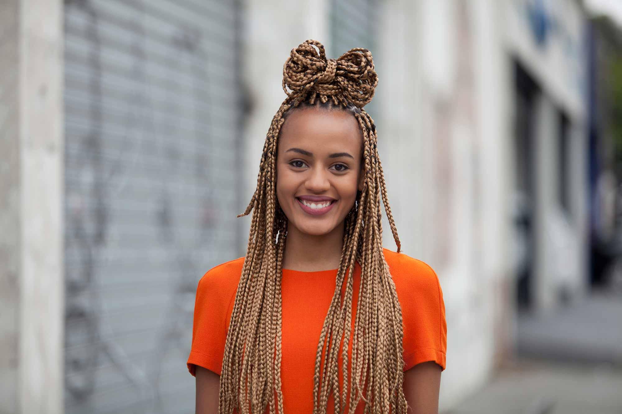 Longue boîte tresse les coiffures : Modèle souriant avec de longues tresses en boîte dorée dans une coiffure à mi-hauteur, portant un haut orange