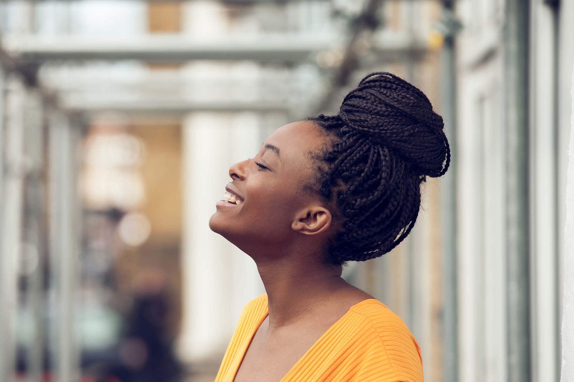 Longue boîte tresse les coiffures : Profil latéral souriant d'une femme avec de longues tresses en forme de boîte marron foncé dans un chignon haut, portant un haut jaune