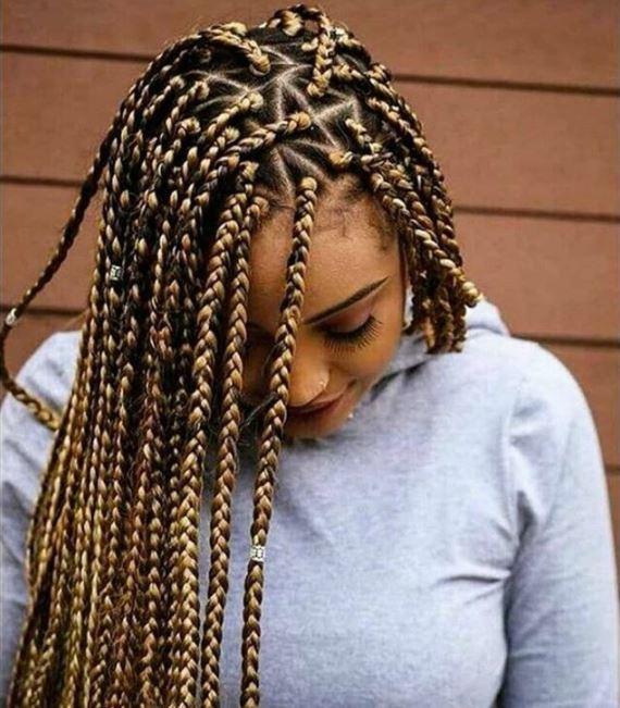 femme avec des tresses en boîte à motif de triangle brun doré sur cheveux naturels