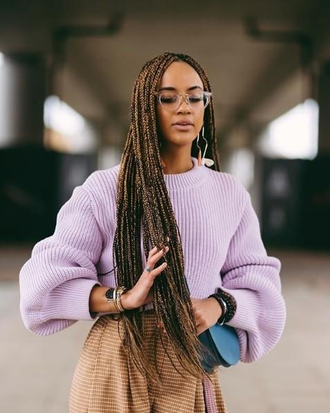 Longues tresses de boîte : Femme avec de très longues tresses de boxe brunes, portant un pull lilas et des lunettes