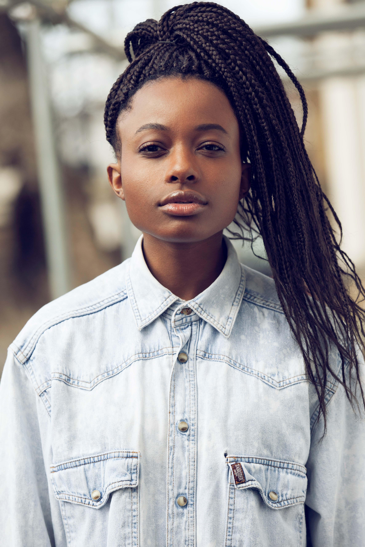 Styles pour les tresses de boxe : jeune femme noire portant une chemise avec des tresses de boxe mises dans une haute queue de cheval