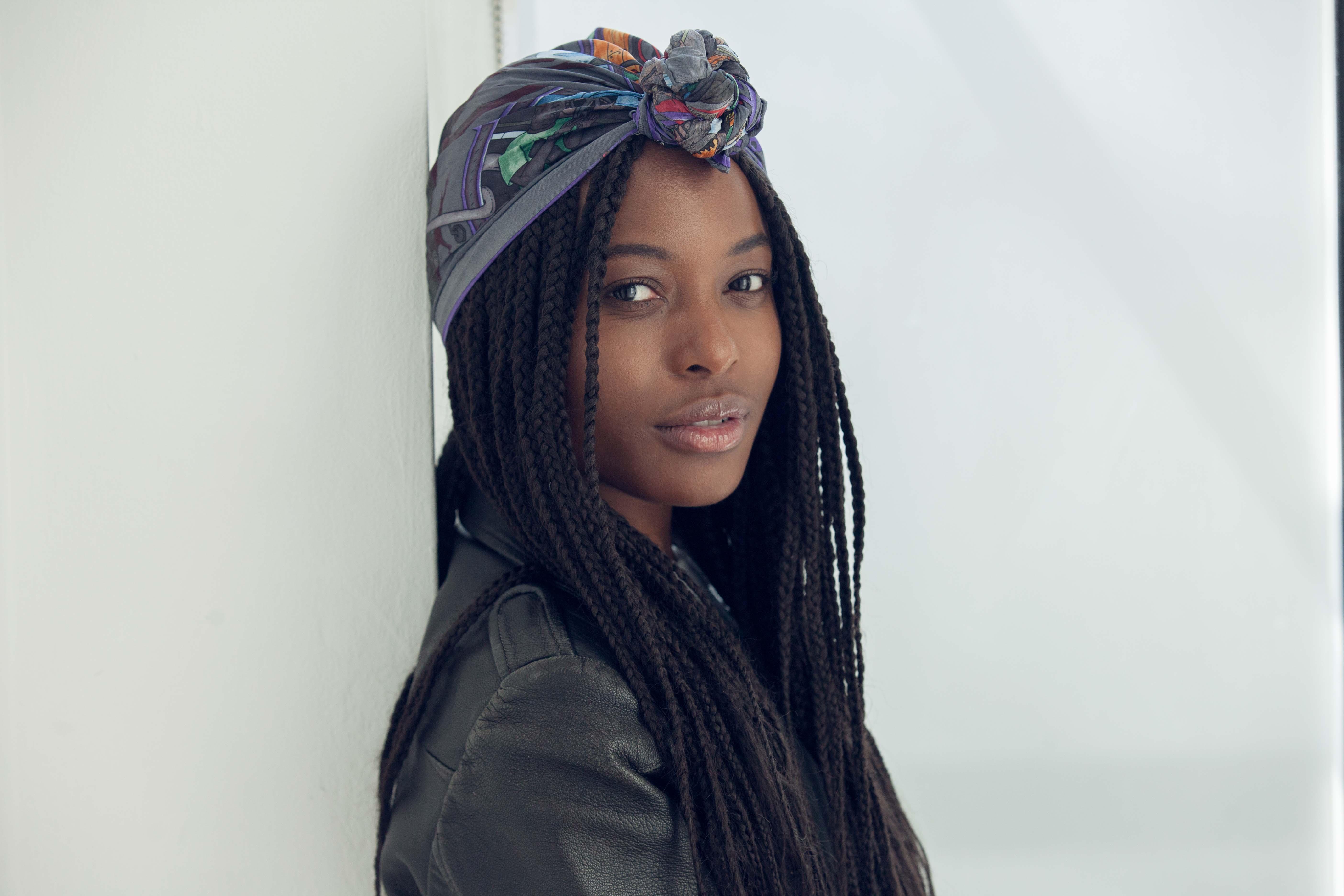 box tresses : jeune femme noire avec des box tresses portant un foulard à motifs