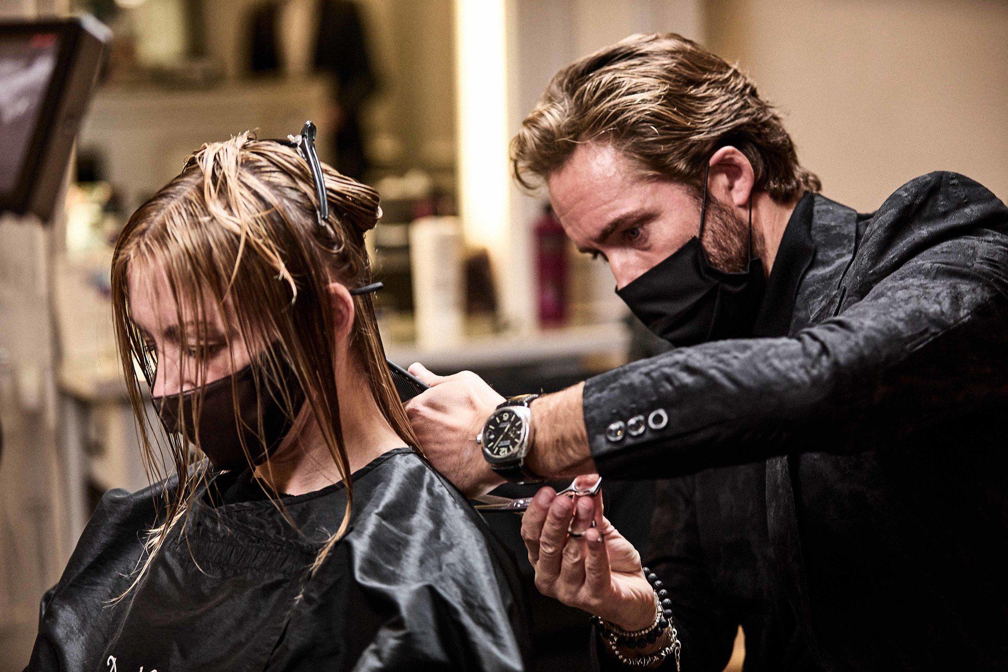Le coiffeur James Brunt coupe les cheveux d'une femme blonde