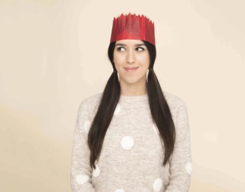 Coiffures de Noël : Femme aux longs cheveux noirs en nattes, portant un chapeau de Noël et un pull en tricot à pois.