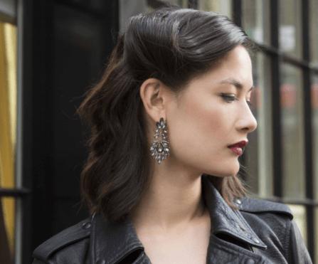 Coiffures de Noël : Femme aux cheveux châtain foncé en rouleau rétro glamour vintage, portant une veste en cuir noir et des boucles d'oreilles ornées de bijoux.