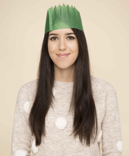 Coiffures de Noël : Femme brune aux longs cheveux bruns et raides, portant un chapeau de fête vert et un pull tricoté à pois.