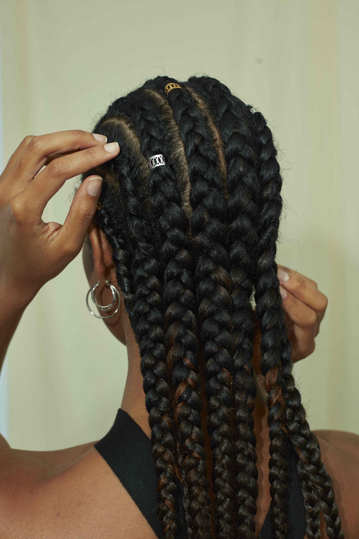 Femme avec ses cheveux de type 4a tressés en cornouillers