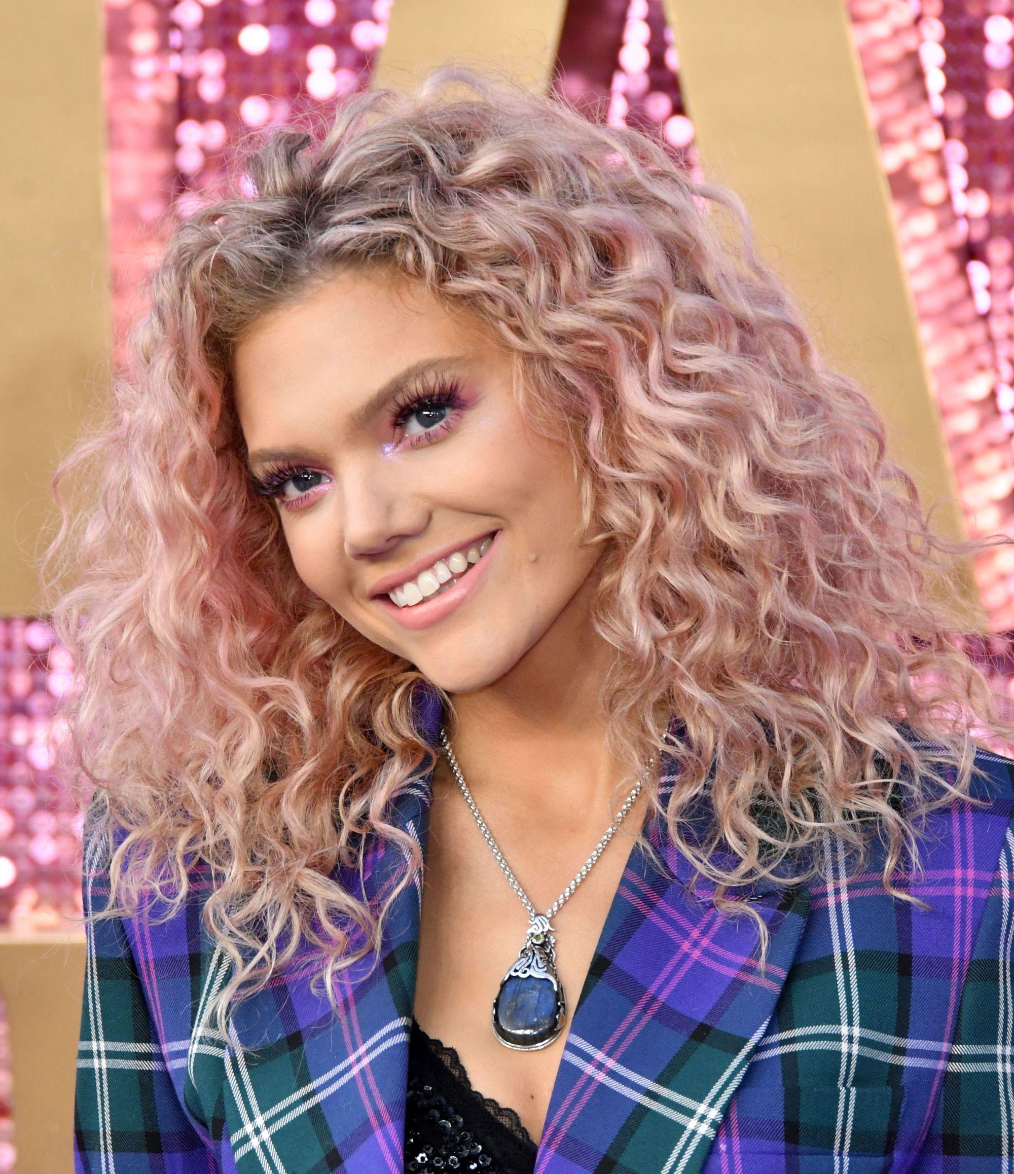 Becca Dudley aux cheveux bouclés rose pastel