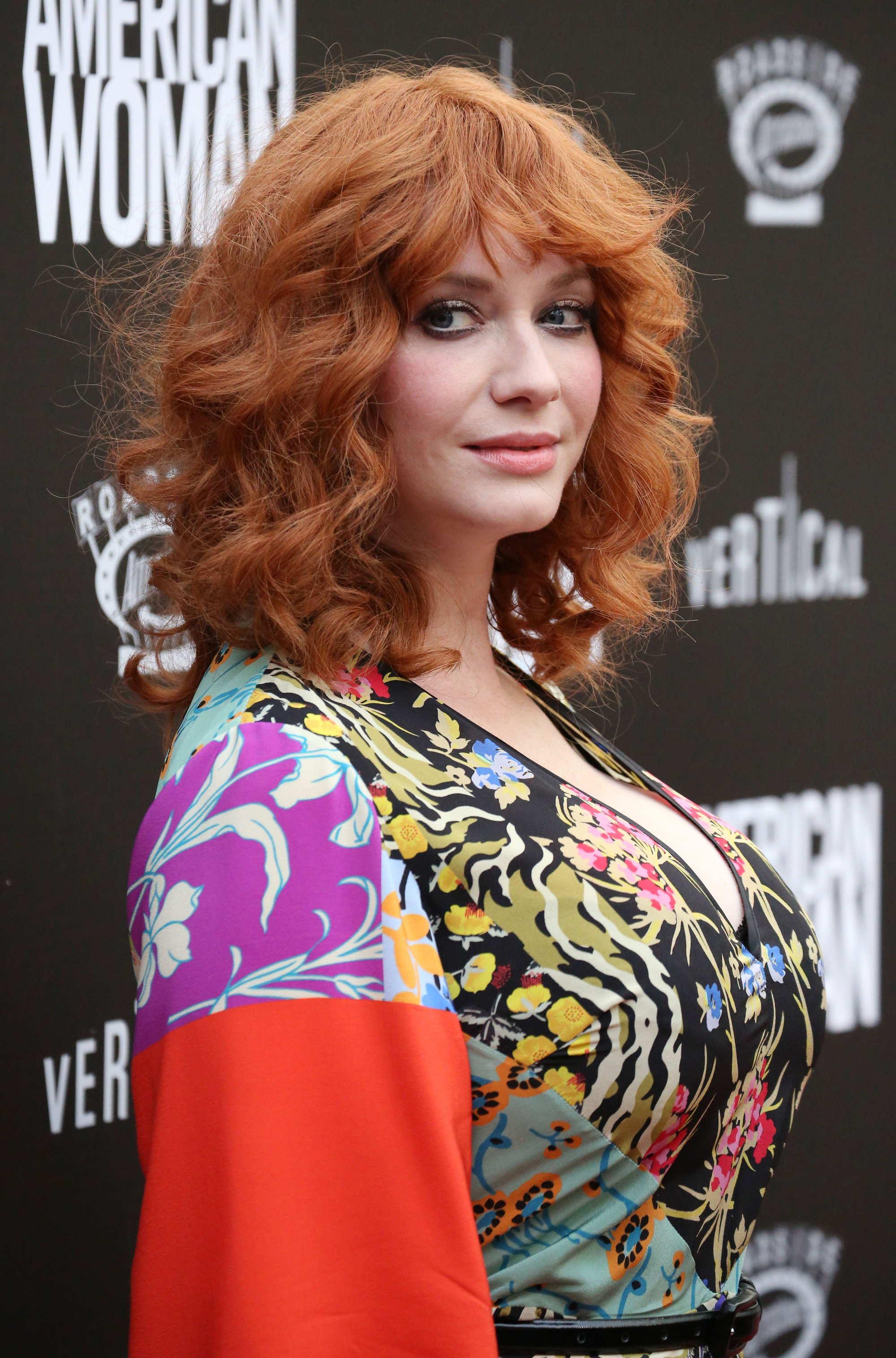 Christina Hendricks avec des cheveux roux bouclés et une frange