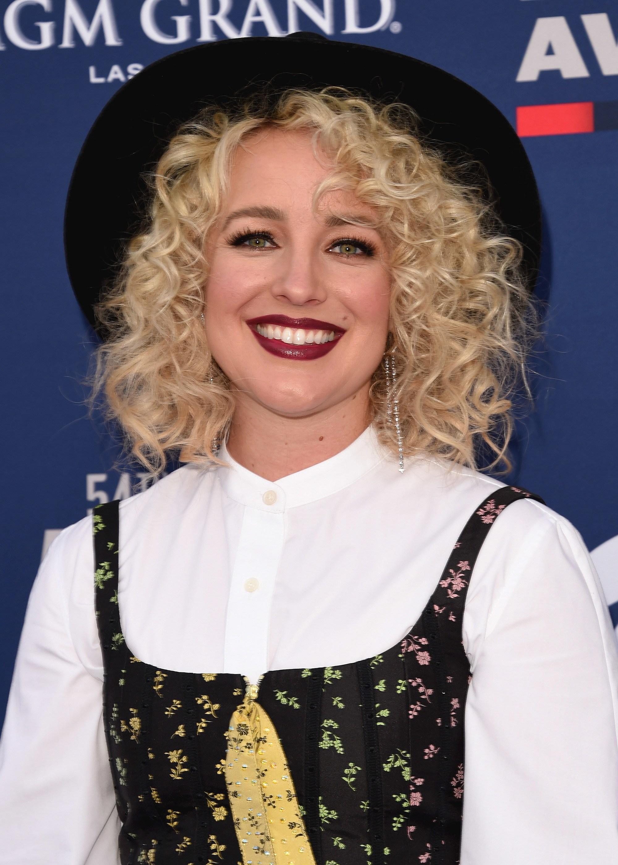 Femme aux cheveux blonds et bouclés aux épaules