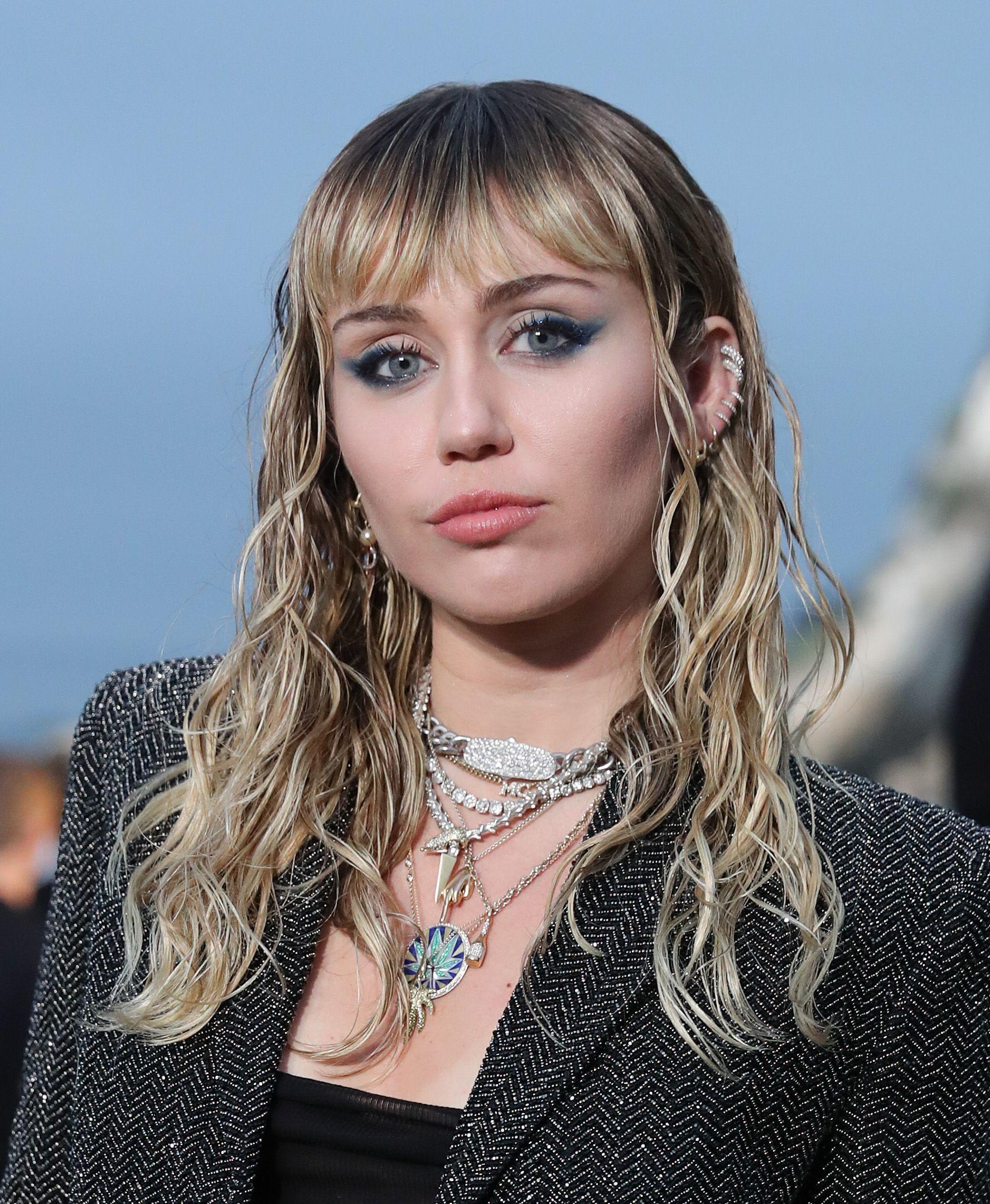 Miley Cyrus aux cheveux blonds ondulés avec frange