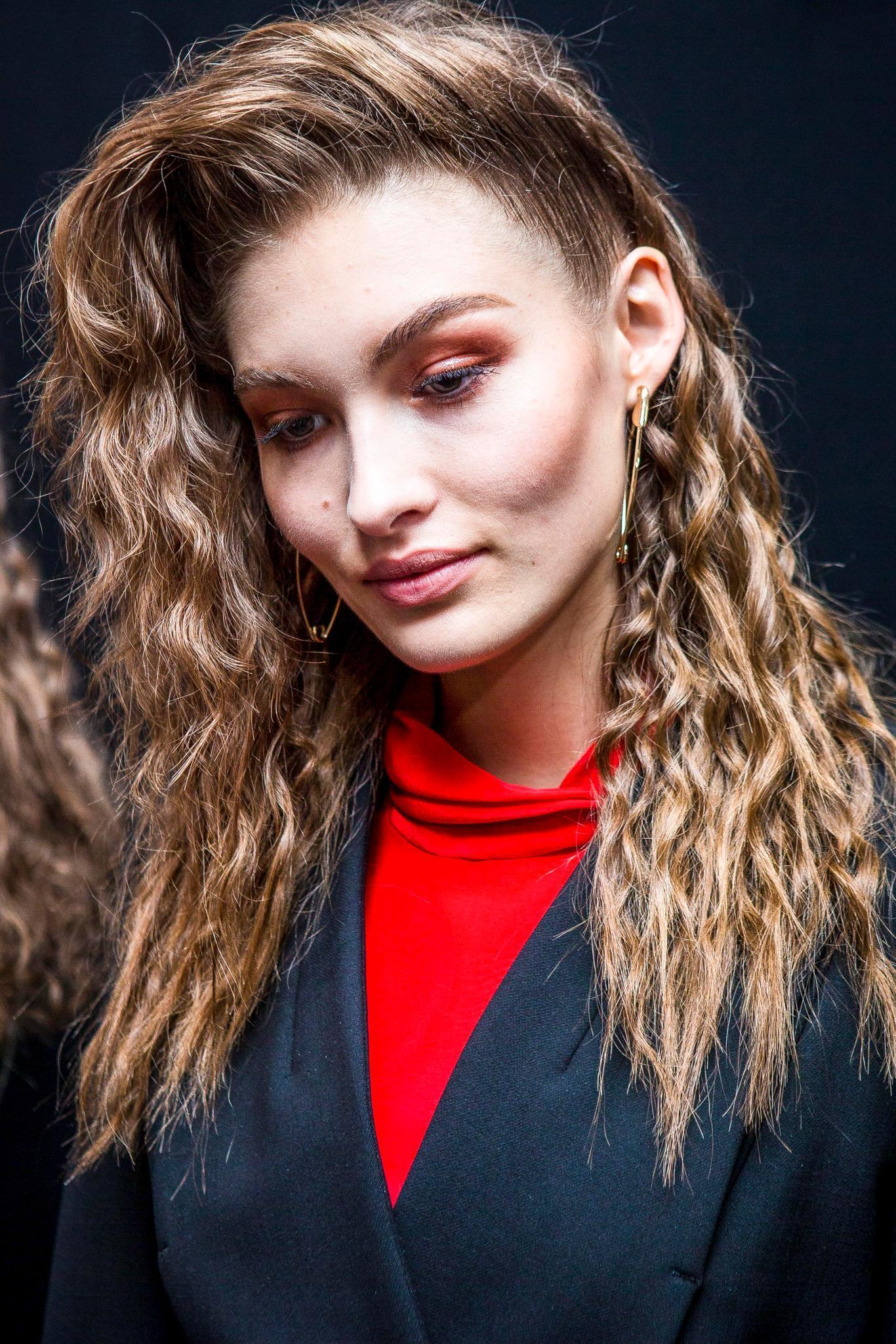 Modèle avec des cheveux ondulés brun clair de longueur moyenne