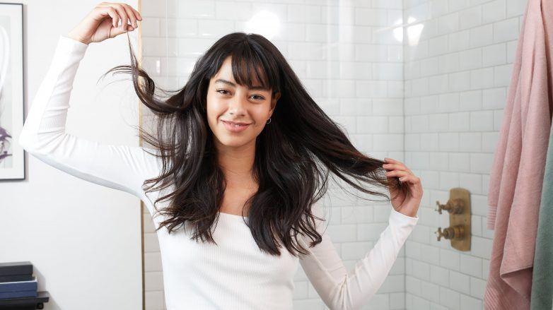 Femme aux cheveux bruns foncés ondulés avec une frange