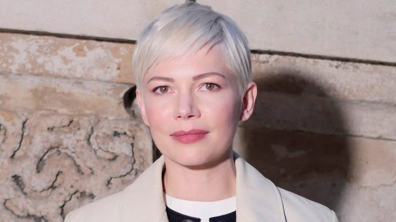 Michelle Williams avec une courte coupe de lutin platine, portant un trench-coat beige