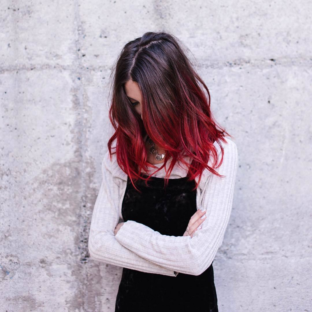 Femme de couleur marron foncé à rouge cerise fondue posant à l'extérieur
