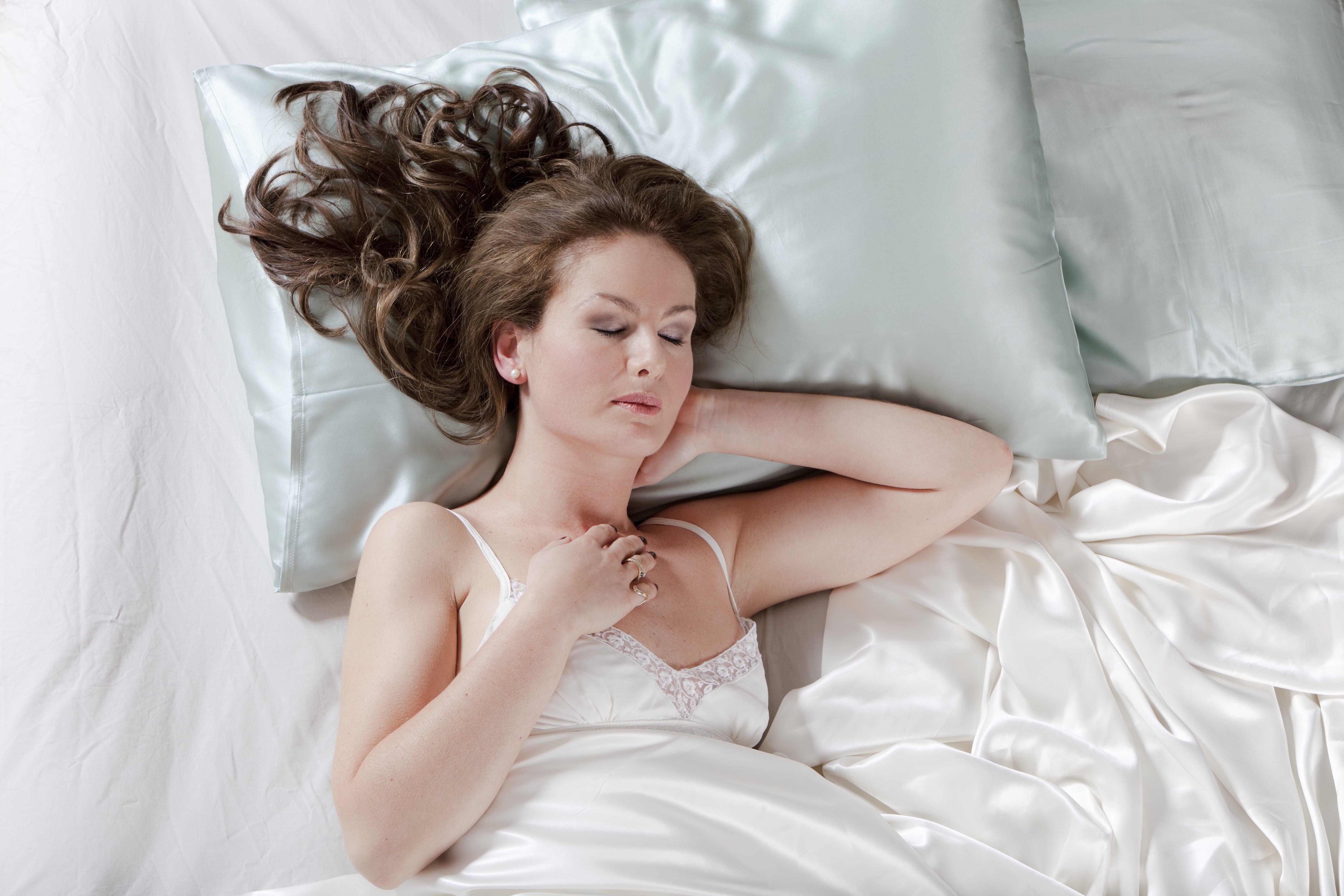 Femme aux longs cheveux bruns ondulés, allongée dans son lit avec des draps de soie.