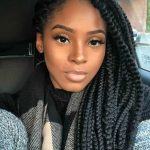 Winter hairstyles for natural hair: Car selfie of a woman with long dark brown dookie braids box braids swept over one shoulder, wearing a patterned scarf