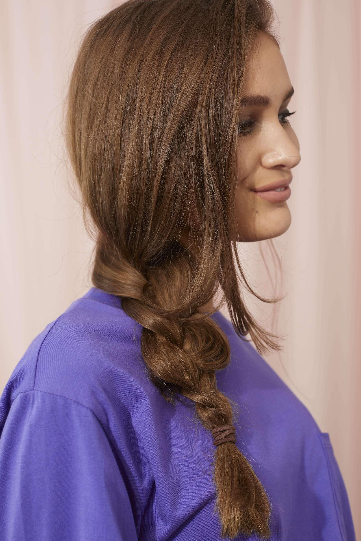 Femme aux cheveux longs brun foncé coiffée en tresse sur le côté