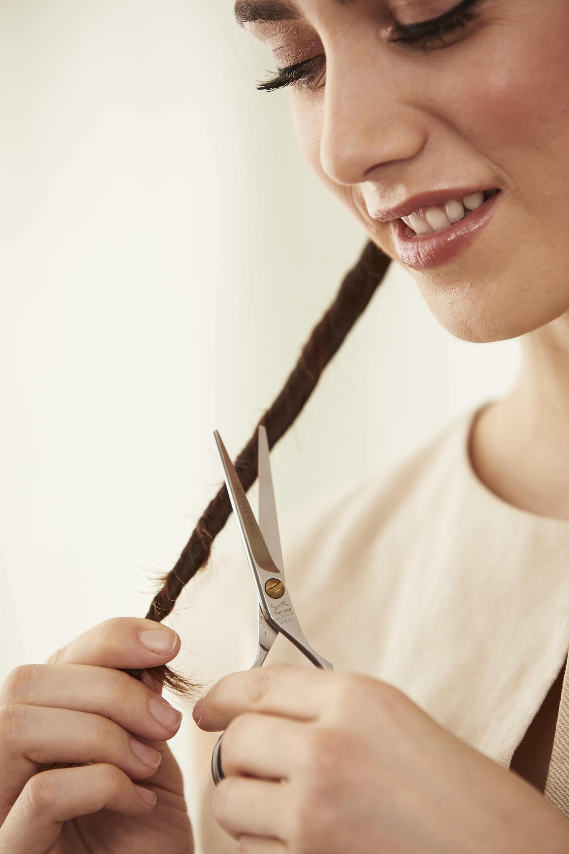 Femme suivant la méthode d'époussetage des cheveux pour couper les pointes fourchues