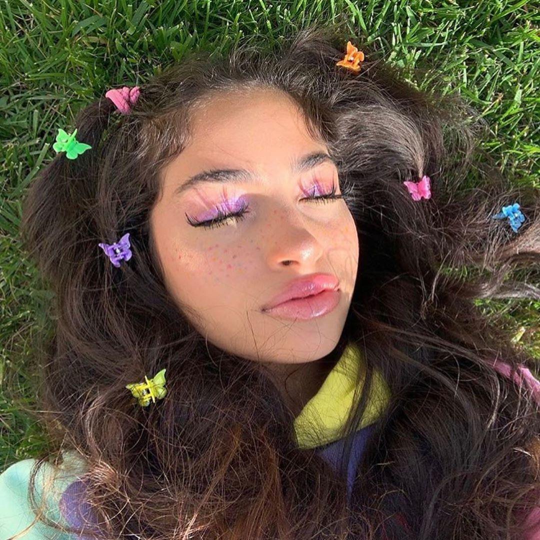 Fille aux longs cheveux bruns couverts de pinces à cheveux en forme de papillon