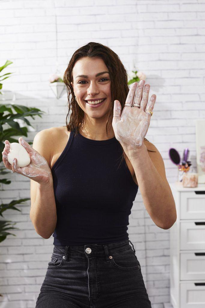 Mannequin brune aux cheveux mouillés tenant une barre de shampoing avec de la mousse sur ses mains