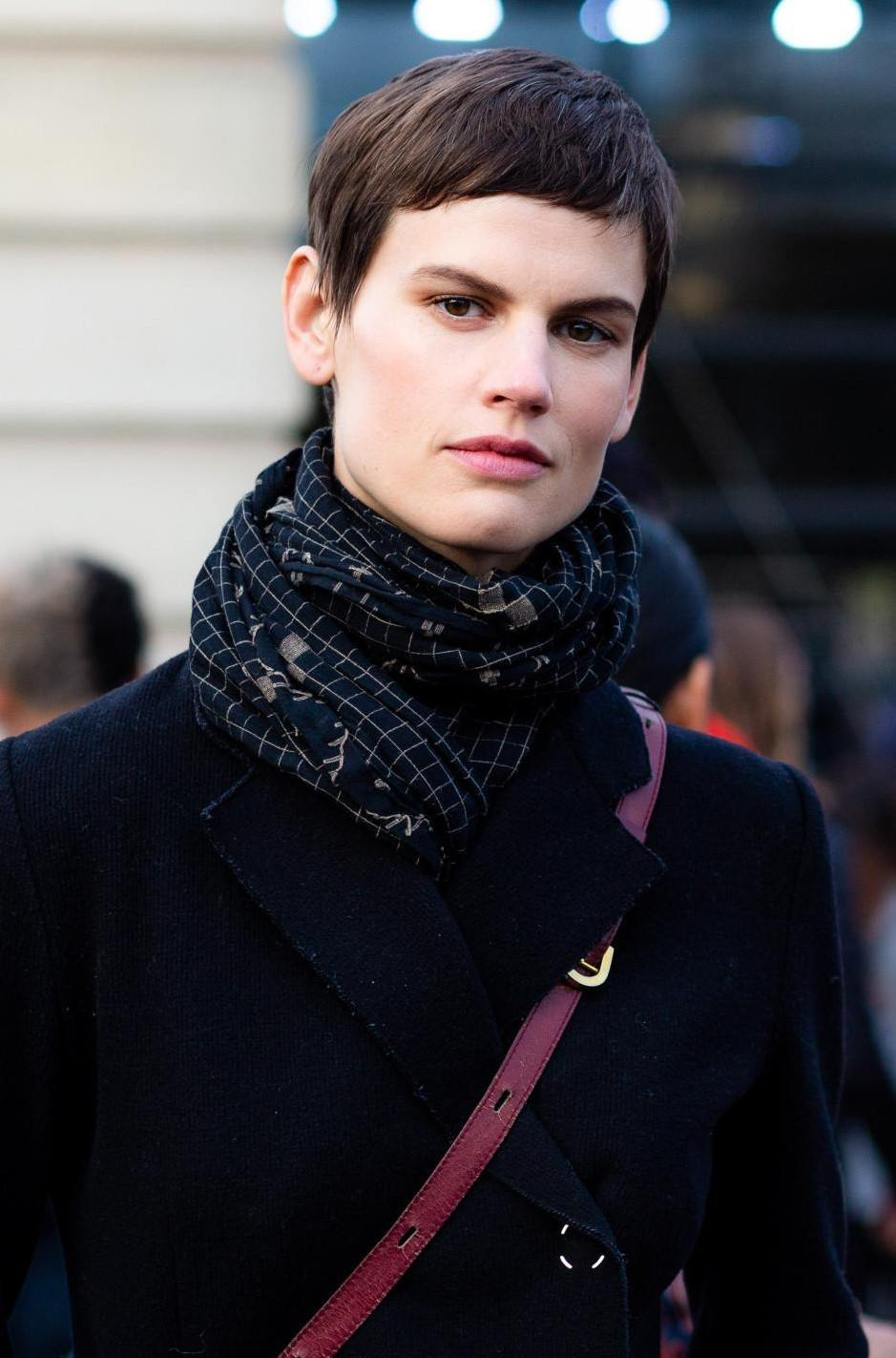 Femme aux cheveux coupés : photo de rue d'une femme brune à la coupe de lutin, à la frange courte, portant un manteau et un foulard