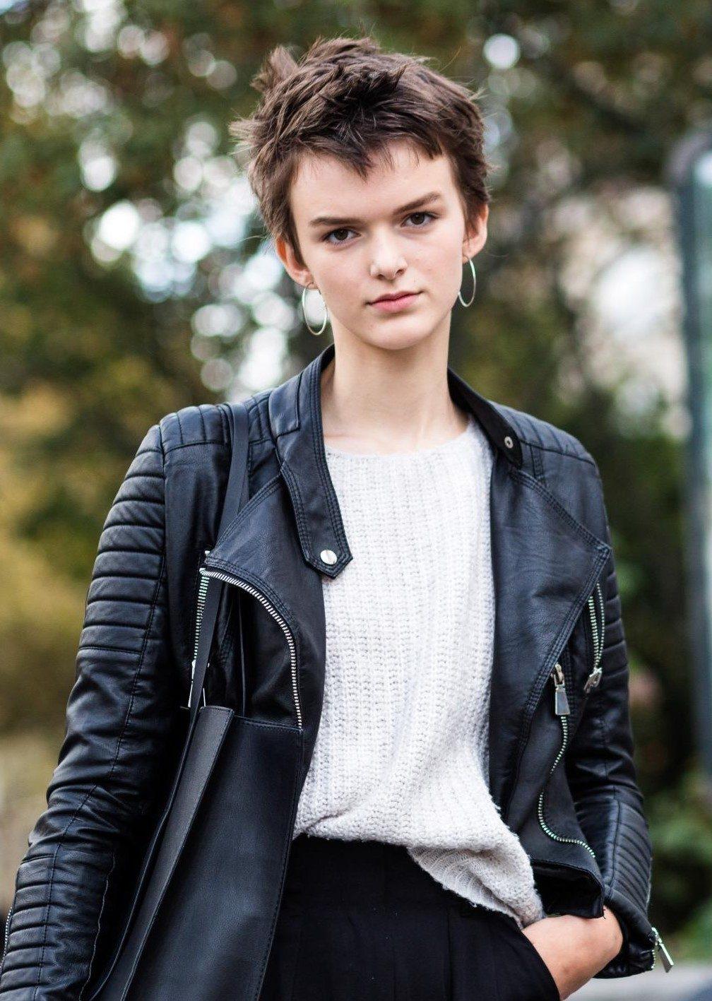 Femme aux cheveux coupés : photo de rue d'une femme aux cheveux bruns texturés coupés, portant un haut blanc et une veste en cuir noir