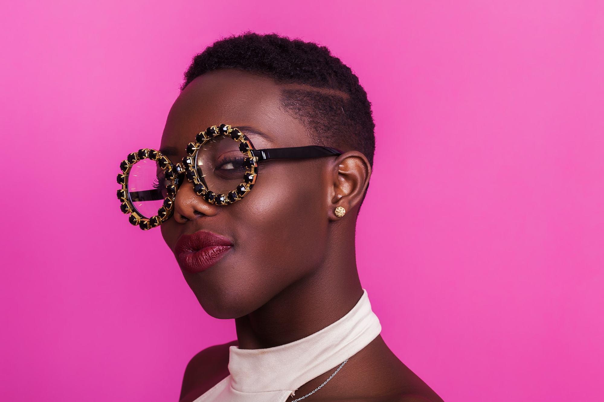 Femme coupée en cheveux : Femme à la coupe afro courte et rasée, portant des lunettes et se tenant sur un fond rose