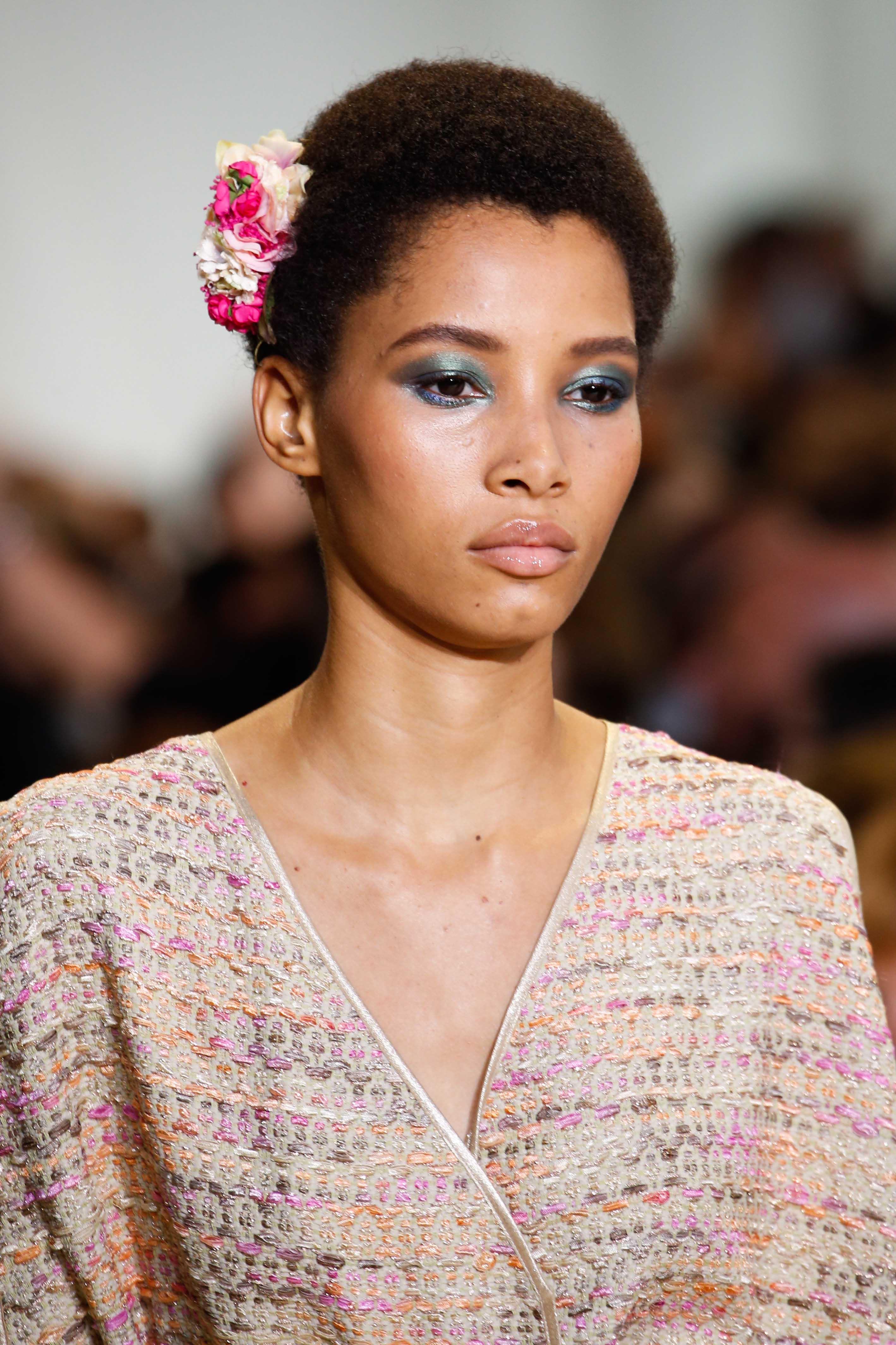 Femme coupée en cheveux : Modèle de défilé avec des cheveux afro bruns courts et un accessoire de fleur rose