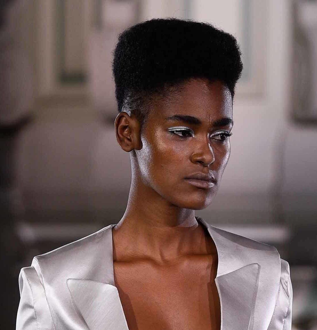 Femme coupée en cheveux : Mannequin de piste avec un afro haut de gamme, portant une veste argentée